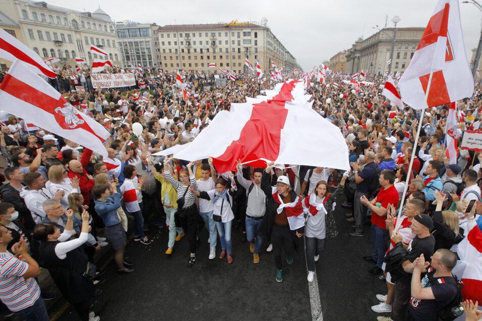 Tausende Demonstranten versammeln sich am 23. August 2020 auf dem Platz der Unabhängigkeit zu einem Protest gegen den Präsidenten Lukaschenko mit einer riesigen historischen Nationalflagge von Belarus.