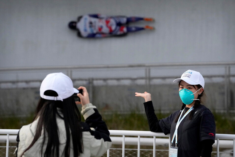 Eine Mitarbeiterin mit Mund-Nasen-Schutz lässt sich während Testrennen im Yanqing National Sliding Center fotografieren.