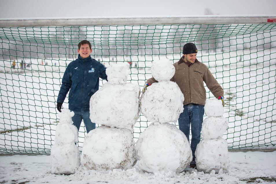 Es schneit in Dresden. Ben (mit Mütze) und Ansgar bauen an den Johannstädter Elbwiesen eine Schneemannfamilie.