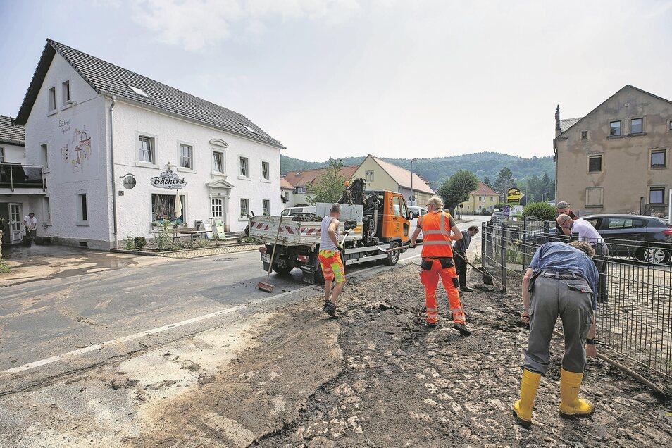 Bauhofmitarbeiter bei Aufräumarbeiten am Dienstag neben der Bäckerei Engelhardt in Neundorf: Der eingetrocknete Schlamm musste mühsam weggeschaufelt werden.