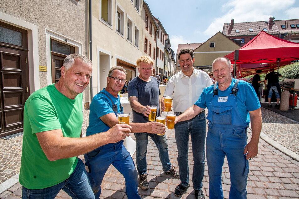 Firmenchef Gerd Andrä (links) und Leisnigs Bürgermeister Tobias Goth (zweiter von rechts) stoßen mit Handwerkern und Anwohnern auf vier gelungene Bauprojekt an.