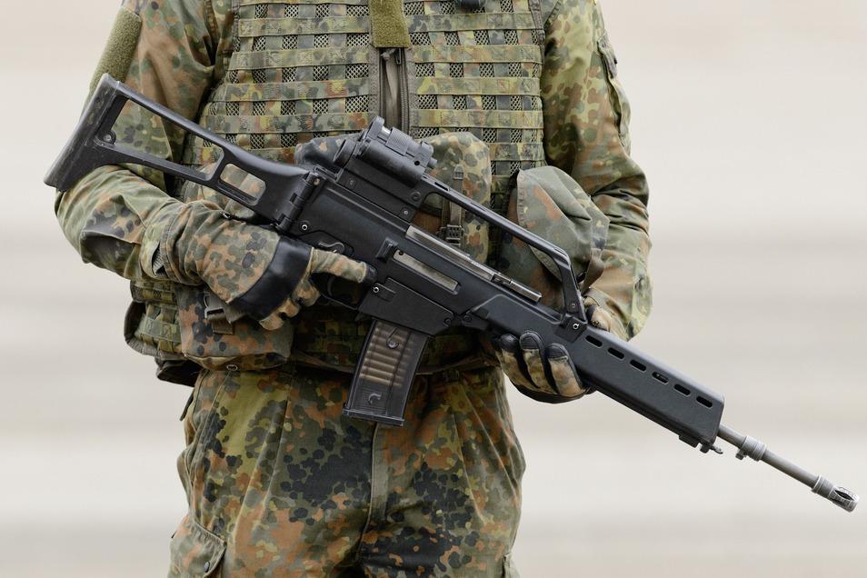 Ein Soldat der Bundeswehr hält ein Gewehr G36 der Firma Heckler & Koch in seinen Händen (hier abgebildet in der verbreiteteren Version mit langem Lauf).