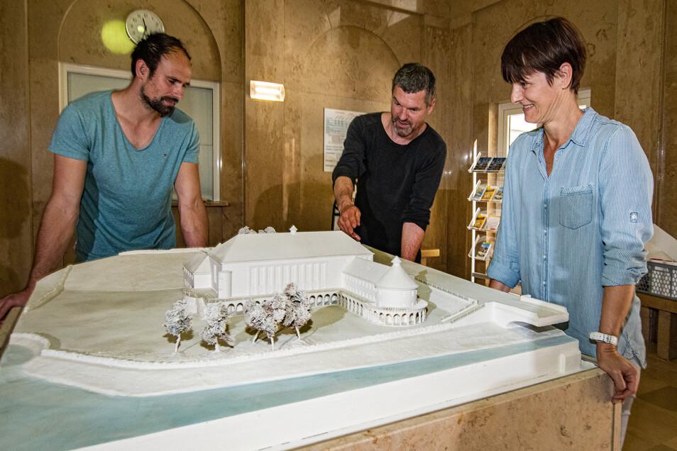 Simone Jentzsch (rechts) von den Stadtwerken und Badleiter Toni Bunzel (links) stehen mit Frank Dornacher an dem fast 90 Jahre alten restaurierten Architekturmodell des Stadtbades. Es wurde jetzt wieder im Foyer wieder aufgestellt.