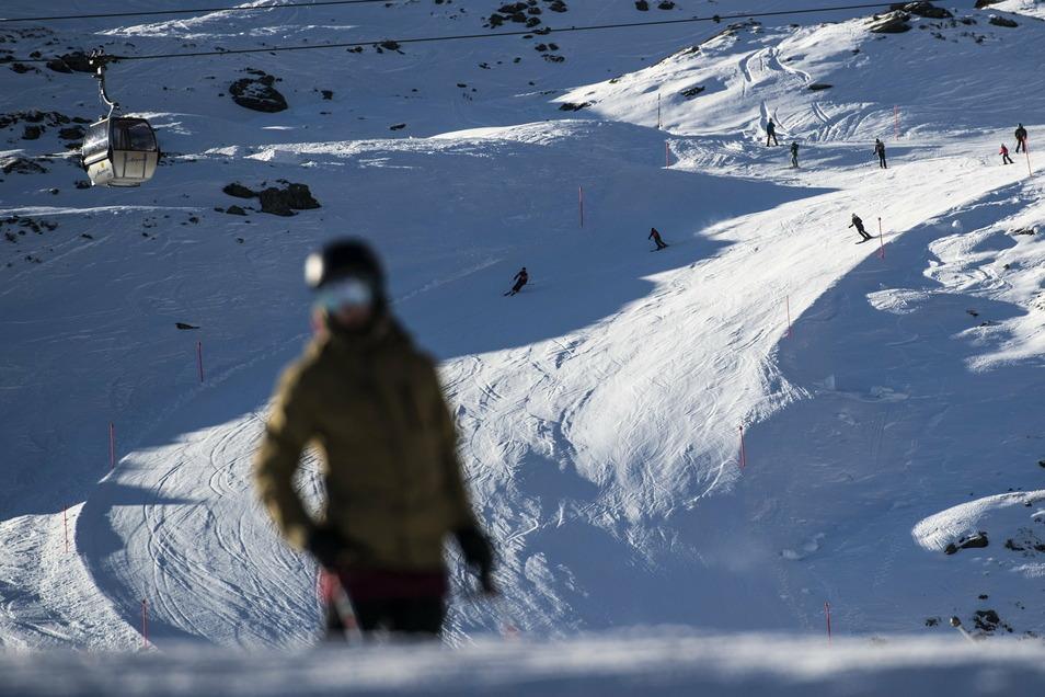 """Skifahrer fahren Ende November den Hang des """"Hoernli"""" in Arosa hinab. Seit dem 28.11.2020 haben in der Schweiz wieder die ersten Skilifte ihren Betrieb aufgenommen. Auch Österreich will seine Skigebiete bald wieder öffnen."""