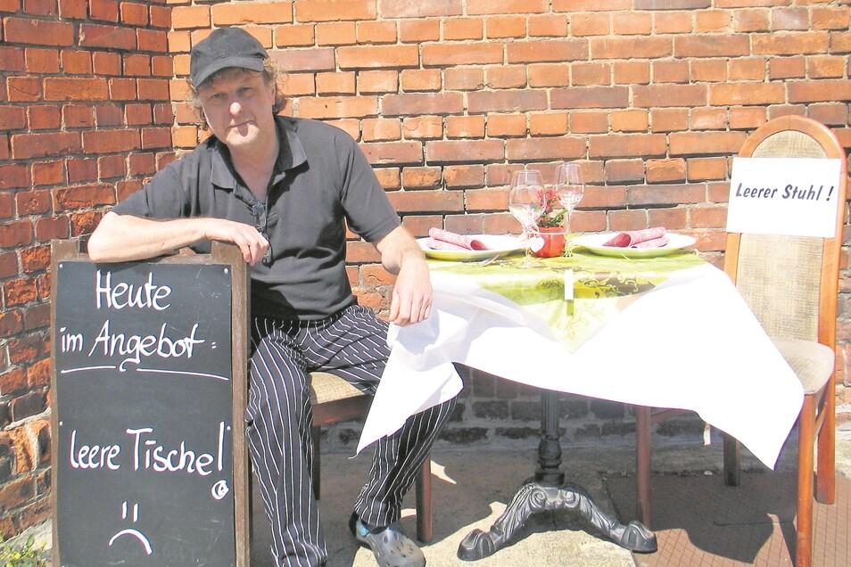 """Dirk Exner, Küchenchef im Turmcafé Weißwasser, ist einer der Organisatoren vom """"stillen Protest"""". An der ungewöhnlichen Aktion beteiligen sich weitere Gastronomen mit leeren Stühlen vor ihren Häusern und Plakaten."""
