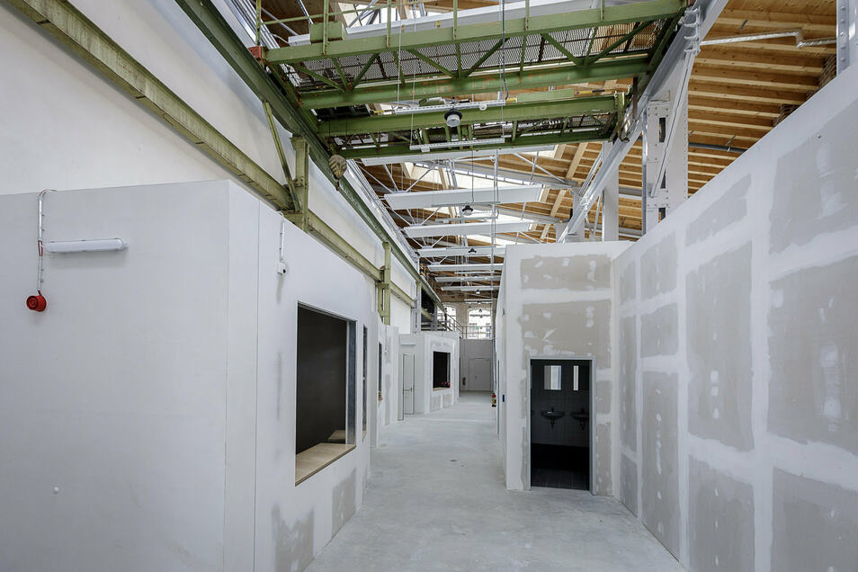 Ein langer Gang erschließt das Zentrum. Die einzelnen Räume stehen als Einbauten mit wärmeisolierten Dächern in der alten Furnierhalle. Die Wände müssen noch gestrichen werden.