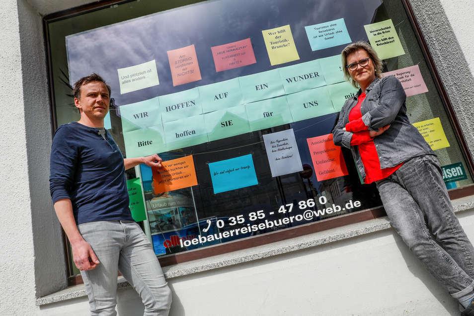 Lars Kohlmann und seine Mitarbeiterin Antje Wendler rufen im Schaufenster des Löbauer Reisebüros zu Solidarität auf. Wenn kein Wunder passiert, ist das Unternehmen bald pleite.