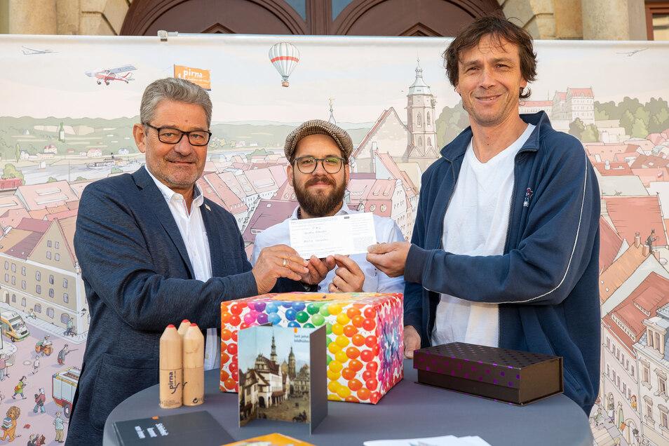 OB Hanke, Böhme und Bierwolf (v.l.) bei der Gewinner-Ziehung: Pirnas Wimmelbild bekommt Zuwachs aus Dresden.