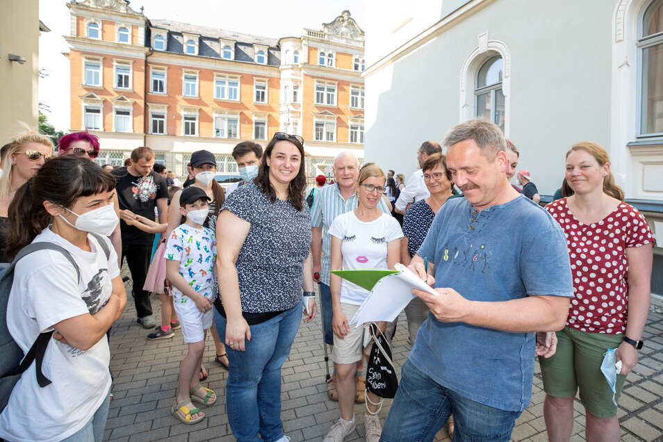 Claudius Rienäcker (2.v.r.) unterschreibt eine Petition gegen die Abschiebung der georgischen Familie I. aus Pirna. Freunde und Nachbarn fordern von Politikern, sie sollen sich für die Rückkehr der neunköpfigen Familie einsetzen.