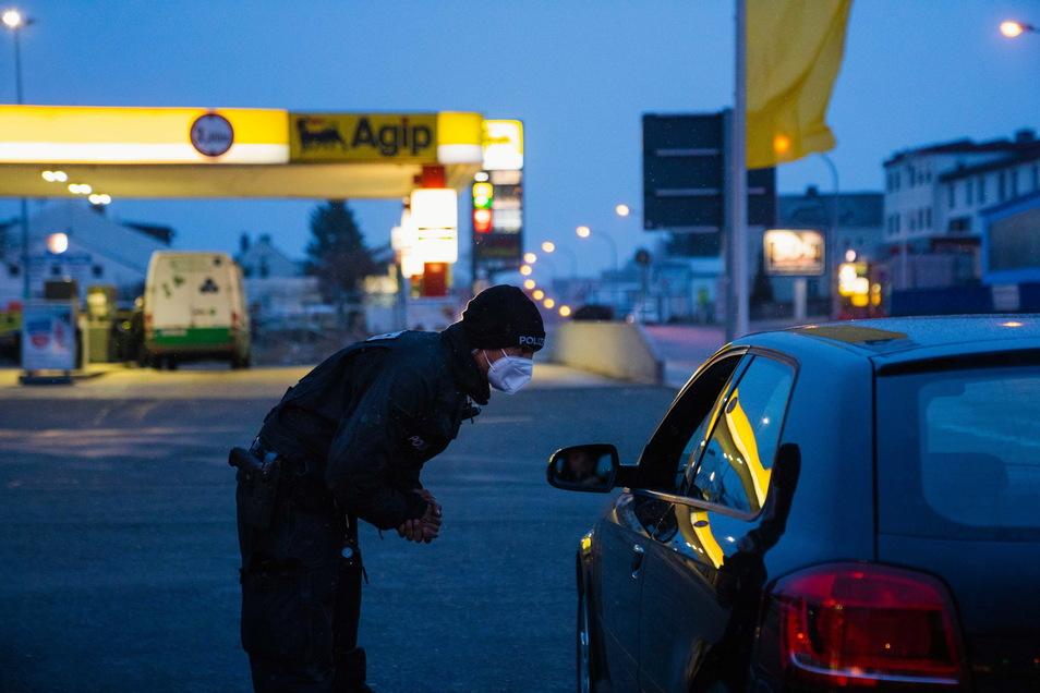 Ein Polizeibeamter in Hof kontrolliert drei Personen in einem Fahrzeug. Aufgrund der anhaltend hohen Inzidenzzahlen finden in Hof verstärkt Kontrollen statt.