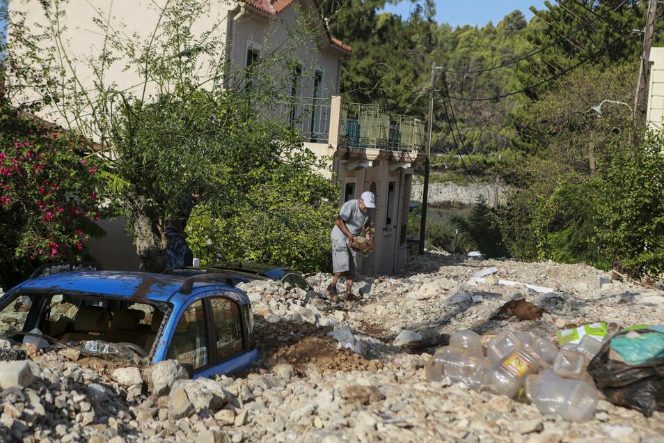 Ein Bewohner Kefalonias räumt durch das Wasser angespülte Steine weg.