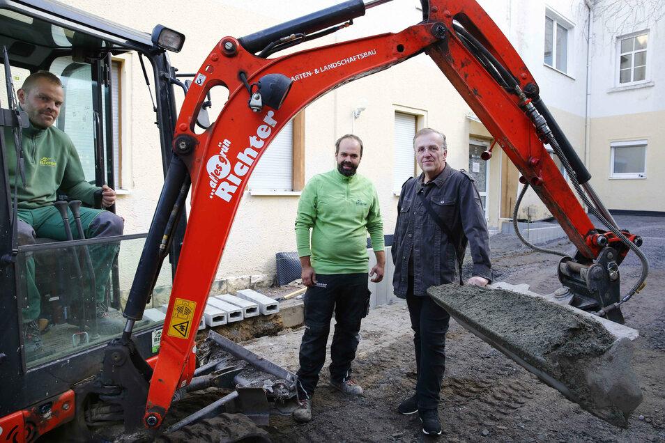 Daniel Mücklich und Benjamin Richter (v.l.) von der Landschaftsbaufirma treffen sich mit Tom Schurig auf dem Gelände des Jugendtreffs zur Baubesprechung.