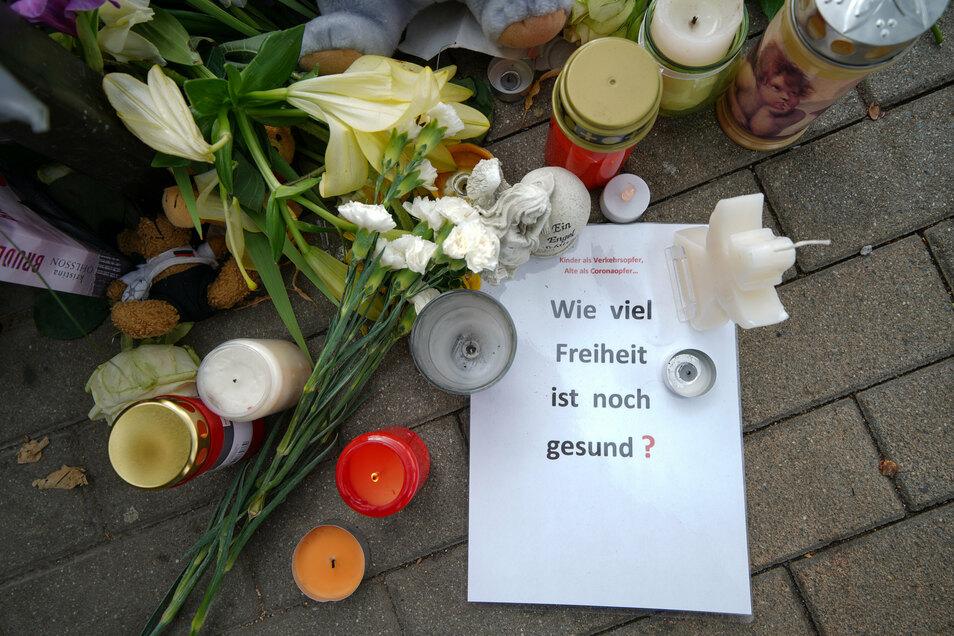 An der Unfallstelle gedenken Menschen mit Blumen, Kerzen und Zetteln dem verstorbenen Kind. Manche Prangern auch die Geschwindigkeit der Fahrer an.