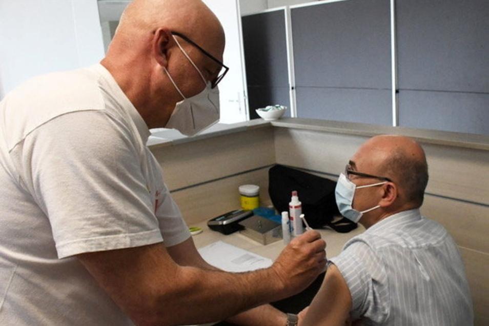 Impfstraße bei Feralpi: Betriebsarzt Dr. Peter Fabritius impft Pietro Perini, Direktor Schrotteinkauf bei Feralpi Stahl.