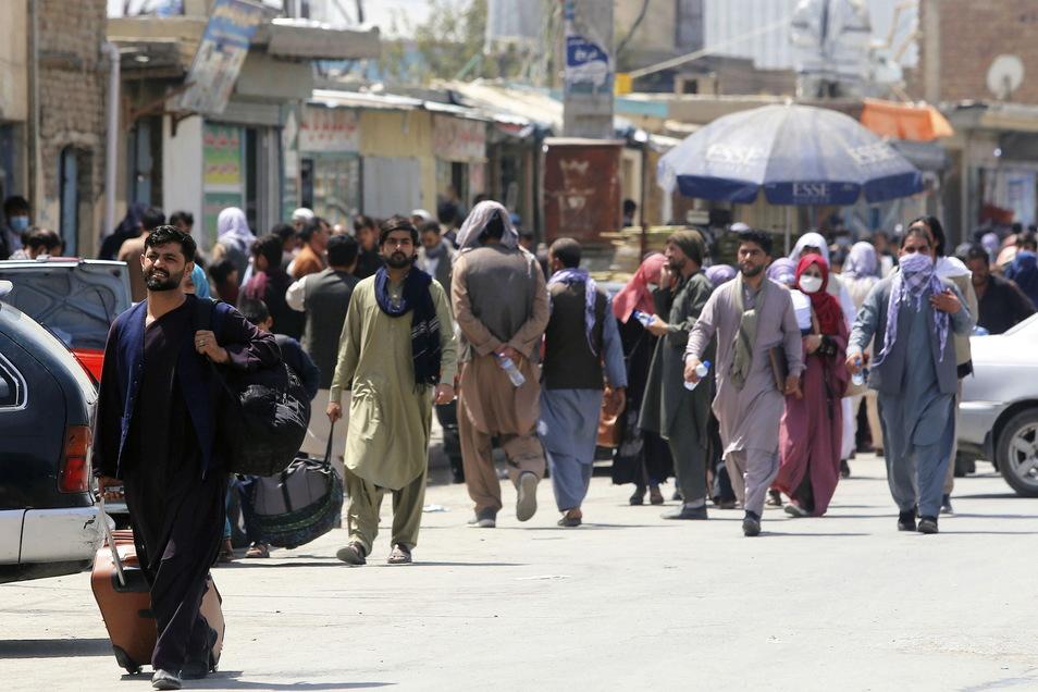 Menschen begeben sich zu einer Militäreinrichtung auf einem Flughafen in Kabul.