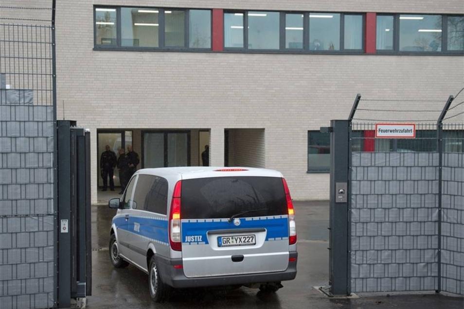 Ein Fahrzeug der Justiz fährt durch ein Tor des Gerichtsgebäudes des Oberlandesgerichts.