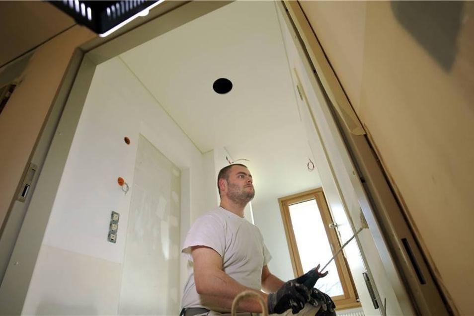 Daniel Schlenker verpasst dem Türrahmen noch den passenden Anstrich.