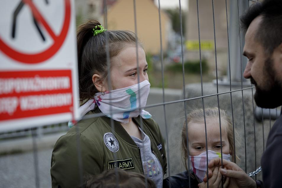Ein polnischer Vater, der in Görlitz arbeitet, trifft am provisorischen Grenzzaun seine Kinder, die in Zgorzelec wohnen.