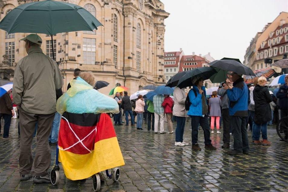Im Regen hatten sich die Pegida-Anhänger vor der Frauenkirche versammelt. Diesmal gab es aber keinen Gastredner, dessen Sprüche lautstark beklatscht werden mussten.