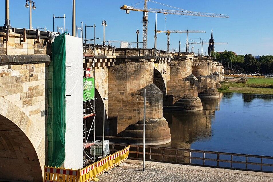 Verhüllt ist der erste Pfeiler der Augustusbrücke auf dieser und auf der anderen Seite. Darunter sanieren die Bauleute die Sandsteinflächen.
