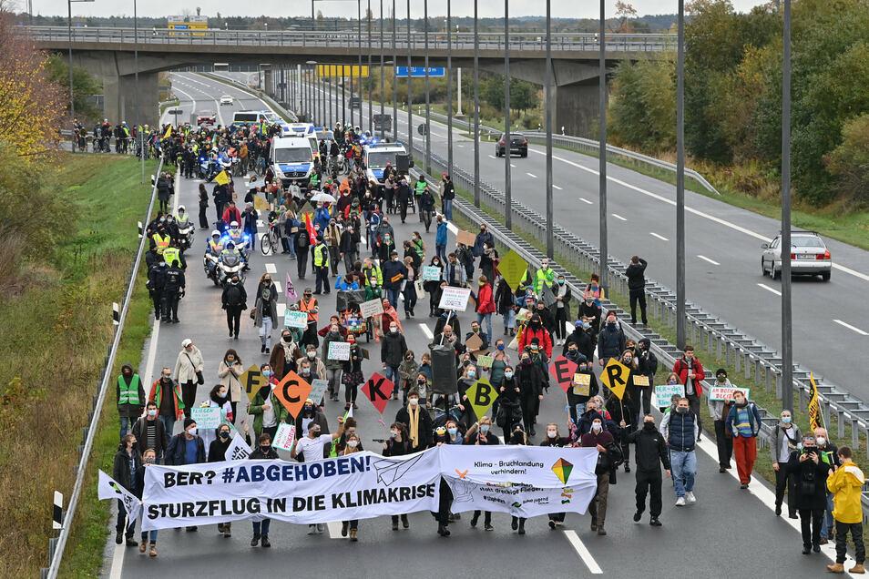 Demonstranten laufen auf einer Straße in Richtung des Hauptstadtflughafens Berlin Brandenburg.