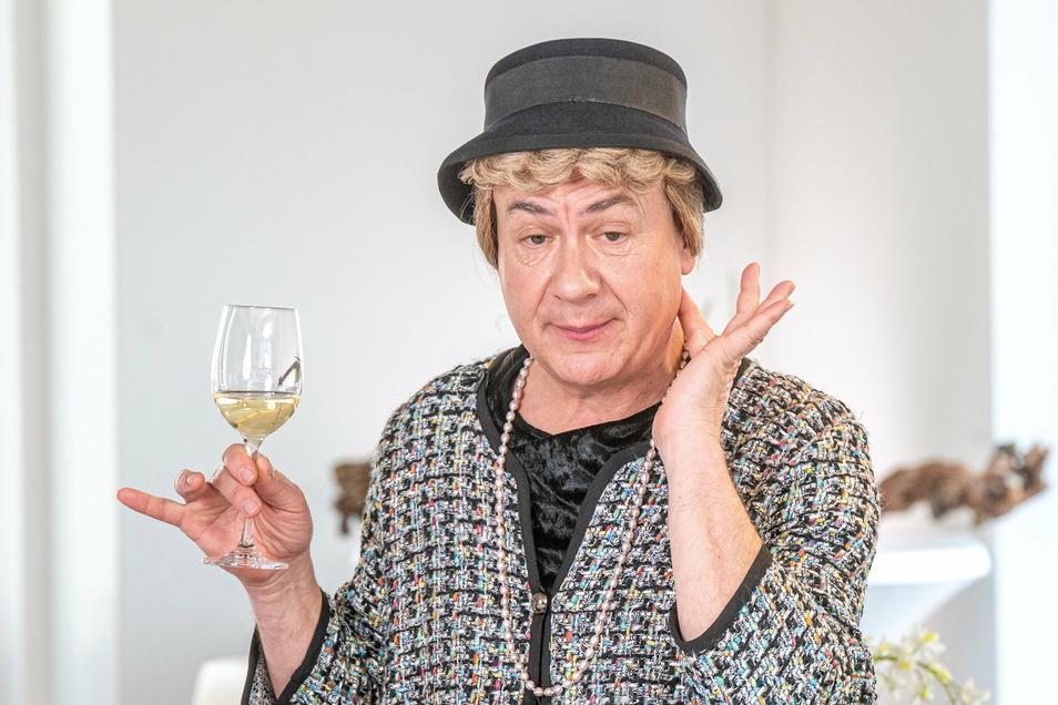 Ilse Bähnert (Tom Pauls) kann auch feine Dame – mit einem edlen Tropfen, der beim Dreh der Weinprobe der Elbland Philharmonie nur Apfelsaft war.