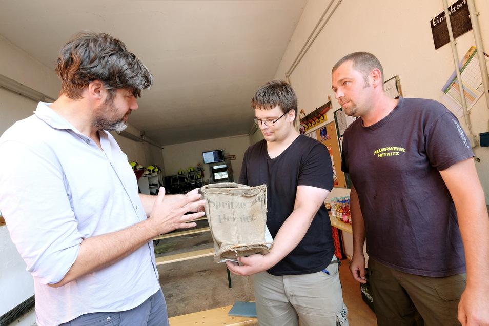 Historiker Clemens Tangerding (links) und die Kameraden Marcel Langenbacher (rechts) sowie Oliver Klengel begutachten einen alten Löscheimer.