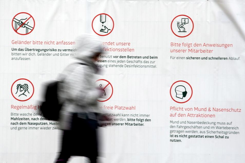 Eine Frau geht in Düsseldorf an einem Plakat mit Hinweisen zum Schutz vor dem Coronavirus vorbei. Die Impfungen nehmen zu und es werden Lockerungen der Corona-Beschränkungen für Geimpfte und Genesene geprüft.