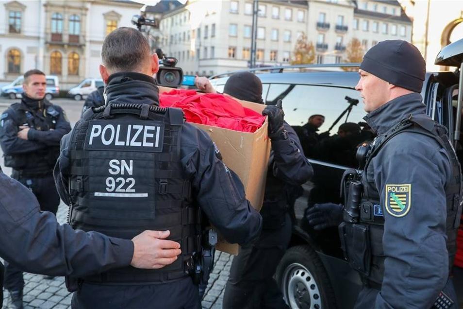 """Polizisten transportieren zur Prüfung eine Kiste mit T-Shirts einer als """"Merkeljugend""""  bezeichneten rechten Kundgebung in Chemnitz ab."""