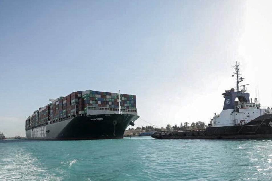 """Das Containerschiff """"Ever Given"""" fährt in Begleitung von Schleppern über den Suezkanal."""