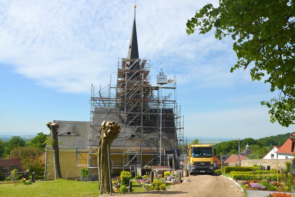 Mitten auf dem Friedhof steht ein Baufahrzeug. Am Freitag hebt ein Kran die goldene Kugel der Turmspitze ab.