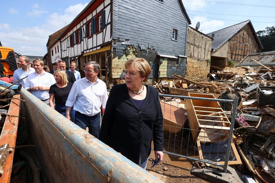 Bundeskanzlerin Angela Merkel (CDU) und Armin Laschet (CDU, 2.v.r), Ministerpräsident von Nordrhein-Westfalen, informieren sich über die Lage im vom Hochwasser betroffenen Stadtteil Iversheim.
