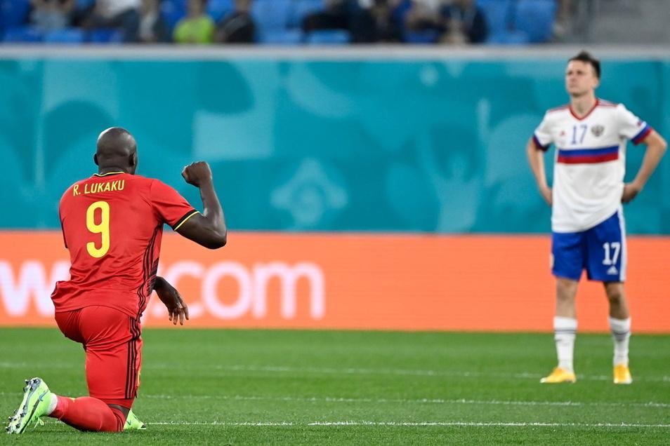 Belgiens Romelu Lukaku (l.) kniet vor dem Spiel gegen Russland nieder und setzt damit ein Zeichen gegen Rassismus. Von den russischen Zuschauern in St. Petersburg wird er dafür ausgepfiffen.