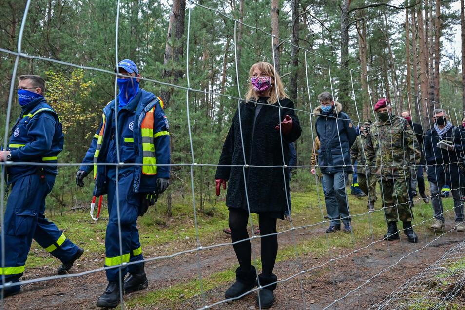 Petra Köpping (M, SPD), Sozialministerin von Sachsen, und weitere Vertreter vom Technische Hilfswerk (THW) und der Bundeswehr begutachten den Bau eines festen Zaunes gegen die Ausbreitung der Afrikanischen Schweinepest.