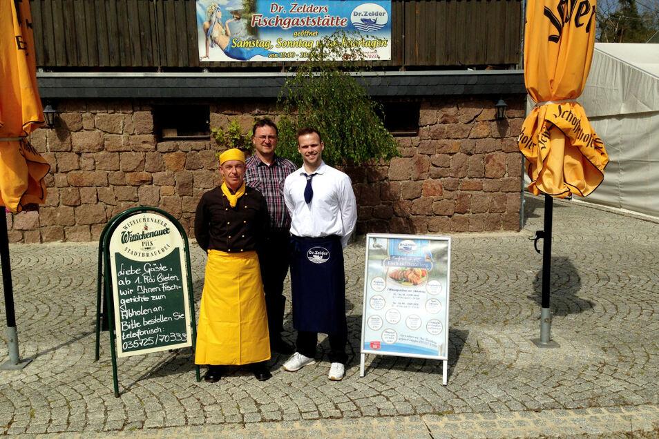 Bieten auch jetzt appetitlichen Fisch an: Chefkoch Sören Paulick (links), Seniorchef Dr. Sebastian Zelder (Mitte) und Betriebsnachfolger Leon Zelder, hier vor der Veranda von Dr. Zelders Fischgaststätte.