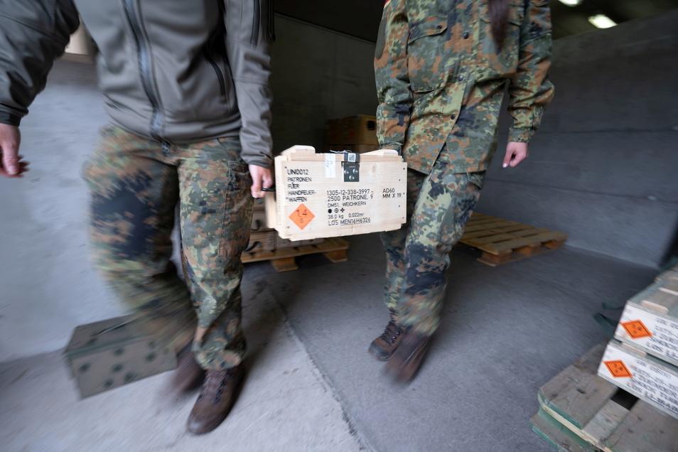 Mitglieder des Kommando Spezialkräfte (KSK) der Bundeswehr tragen eine Munitionskiste aus einem Munitionslager.