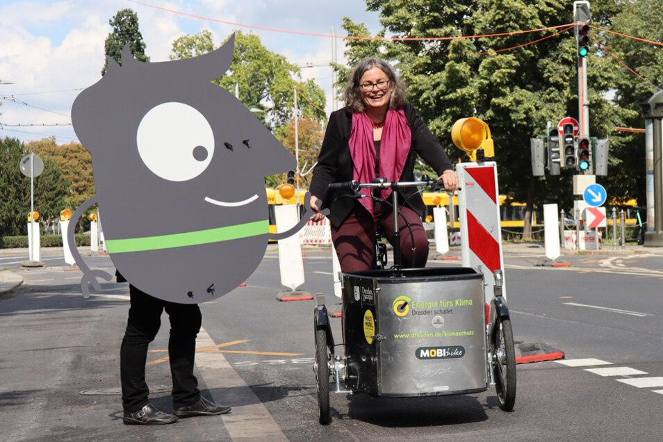 Edgar, das Maskottchen der Mobilitätswoche, zeigt Umweltbürgermeisterin Eva Jähnigen den fast fertigen neuen Radstreifen an der Albertstraße.