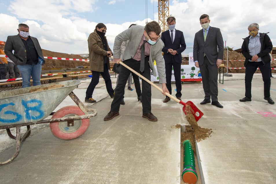 Moritzburgs Bürgermeister Jörg Hänisch (parteilos) gräbt die mit verschiedenen Zeitzeugnissen gefüllte Kapsel in die Bodenplatte des neuen Kinderhauses Kleeblatt ein.