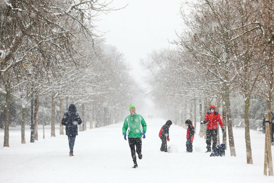 Ein Mann joggt im Schnee im Retiro-Park in Madrid.