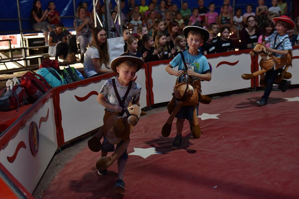 Die Cowboys aus der ersten Klasse galoppieren mit ihren Pferchen durch die Zirkusmanege.