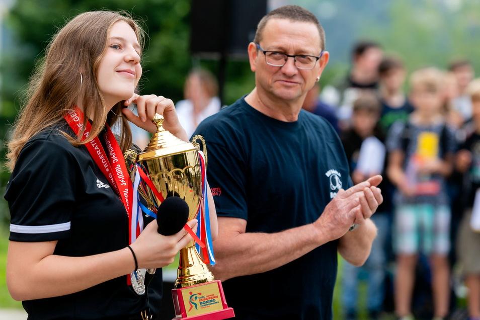 Emely Dittrich mit Pokal und Heimtrainer Heiko Kött. An der Sebnitzer Oberschule wurde sie von ihren Mitschülern und Lehrern empfangen.