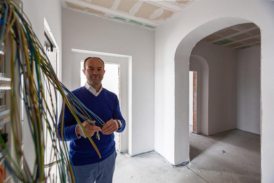 Moderne Technik in historischen Mauern. Falk Kühn-Meisegeier, Chef der Wohnungsgenossenschaft Dippoldiswalde, hält die Kabel einer modernen Medienstation, mit denen alle 16 Wohnungen im alten Landratsamt ausgestattet werden.