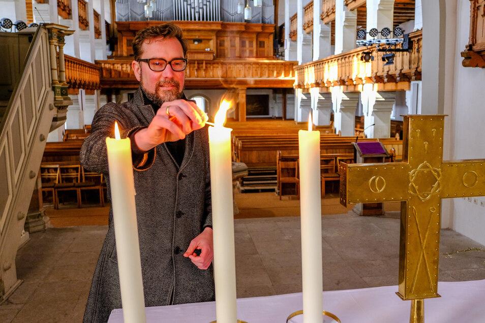Pfarrer Björn Fischer zündet in Radebeul in der Friedenskirche Altarkerzen an.