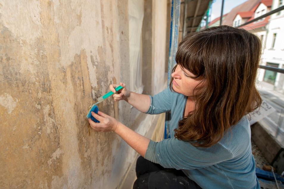 Restauratorin Anja Tomaschewski beim Vornetzen für die Unterfüllung der barocken Fassade.