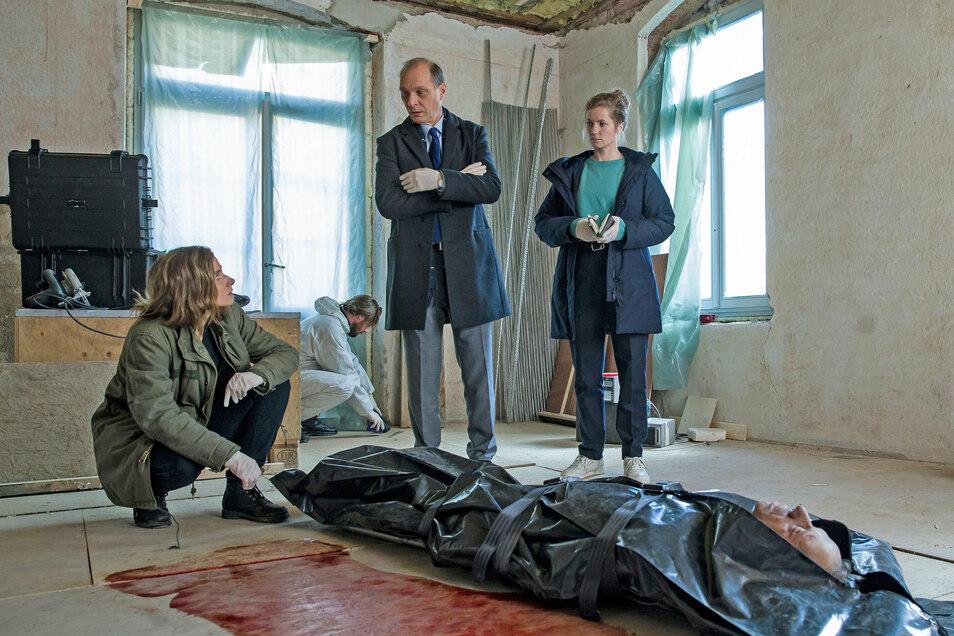Karin Gorniak (Karin Hanczewski, li.), Peter Michael Schnabel (Martin Brambach) und Leonie Winkler (Cornelia Gröschel) nehmen den Tatort und das Opfer in Augenschein.