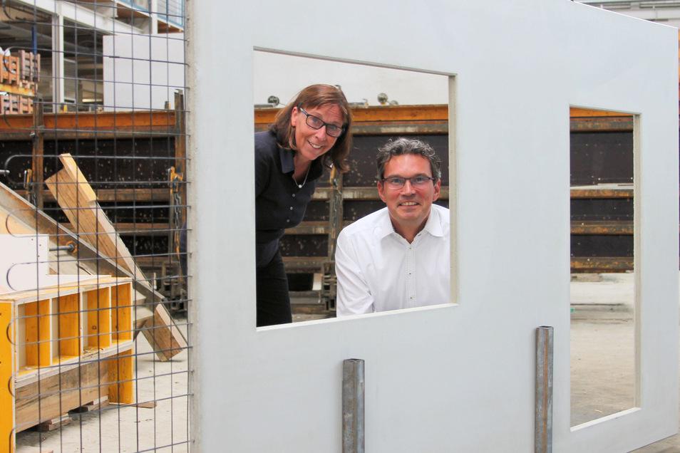 Hier schauen Birgit Zocher (links) und Matthias Schurig, die beiden Geschäftsführer des Betonwerkes Oschatz, durch ein Fenster eines Betonteils, aus dem noch das Carbon herausragt. Die Platte ist mit drei Zentimetern Stärke viel dünner als Stahlbeton.