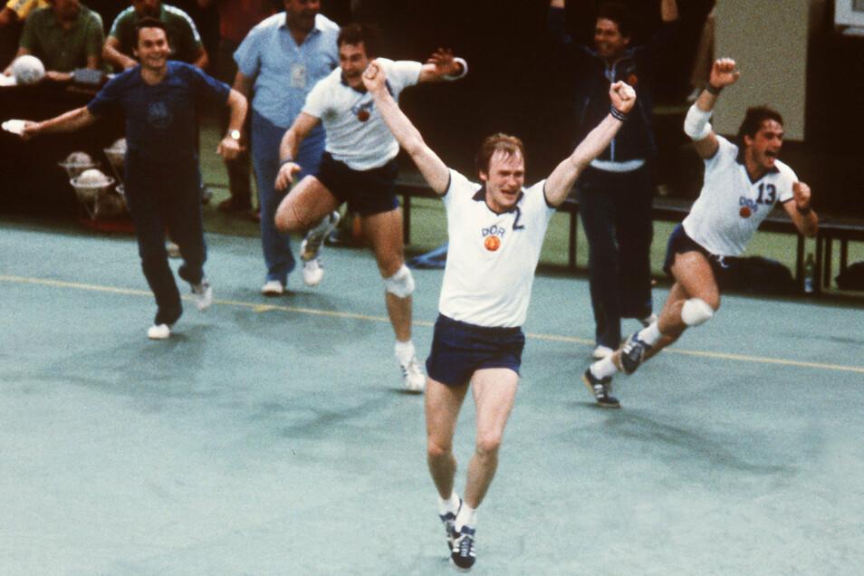 Die DDR-Handballer von Trainer Paul Tiedemann (l.) jubeln über den Olympiasieg, vorn Günter Dreibrodt.