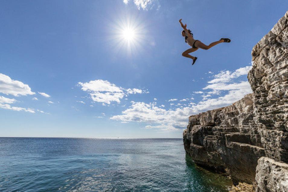Nahe dem kroatischen Städtchen Pula springt ein Mädchen von der Klippe ins Wasser. Wie bevölkert werden die Buchten diesen Sommer?