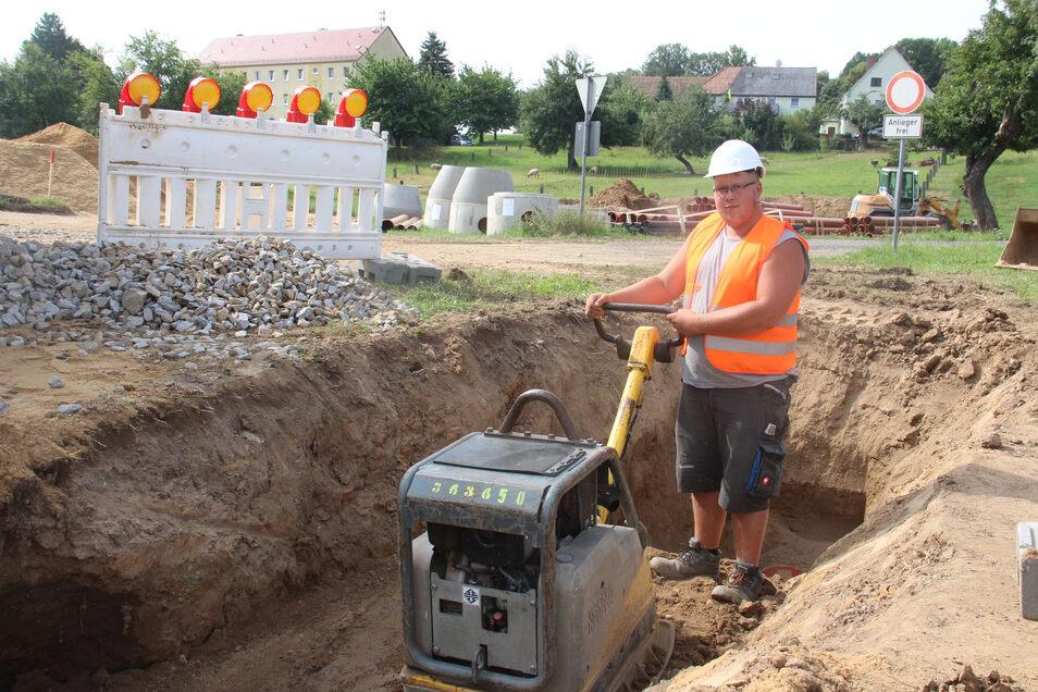 Martin Neu von der Firma Steinle-Bau verdichtet mit einer Rüttelplatte die Erde über einem frisch verlegten Mischwasser-Rohr im Zentrum von Nedaschütz.