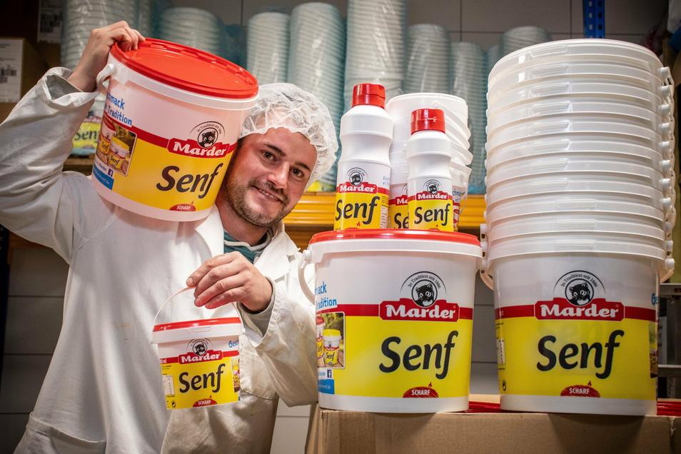 Sebastian Wagner mit den größeren Abpackungen der Senfeimer. Diese werden unter anderem von Großküchen oder der Gastronomie geordert.
